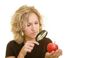Blonde Frau betrachtet einen roten Apfel unter einer Lupe
