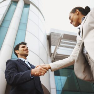 Low angle view of two business executives shaking hands --- Image by © Royalty-Free/Corbis